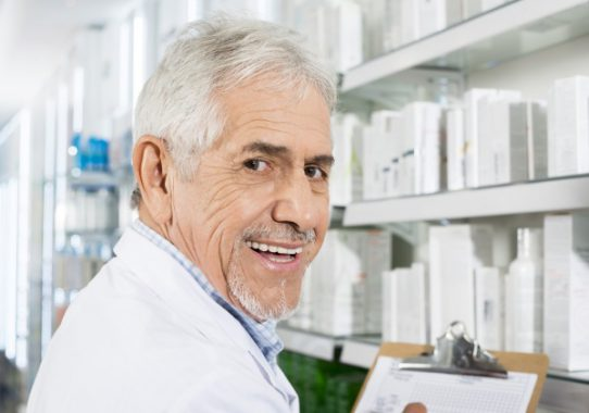 Portrait of confident senior pharmacist counting stock in drugstore