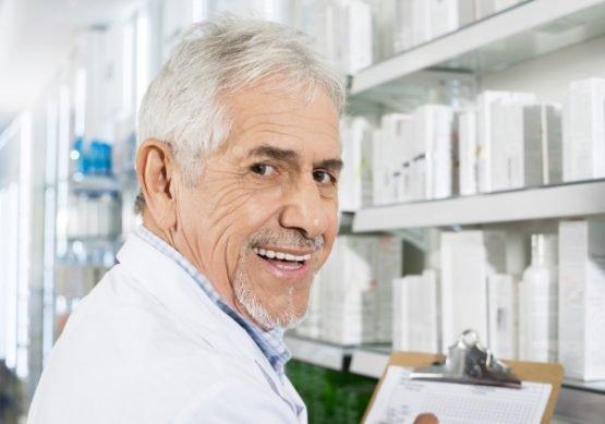 Portrait of confident senior pharmacist counting stock in drugstore