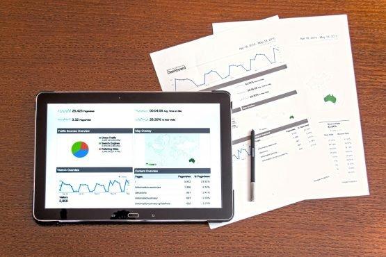 Um tablet e uma série de papéis sobre uma mesa exibem gráficos e números, simbolizando as informações contidas em uma DRE.